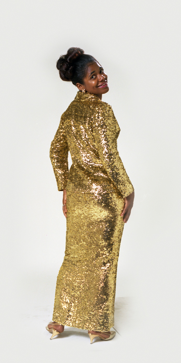 Carla Thomas standing in a gold sequined dress.