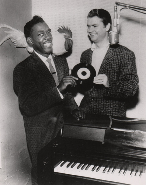 Roscoe Gordon and his chicken and Sam Phillips hold a vinyl record